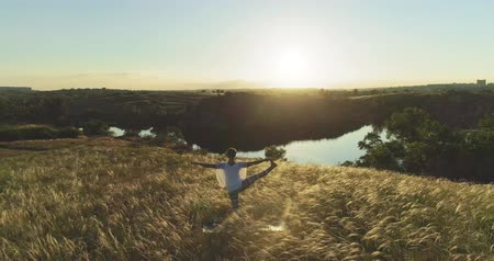 idílio : Girl meditates on a beautiful meadow at sunset