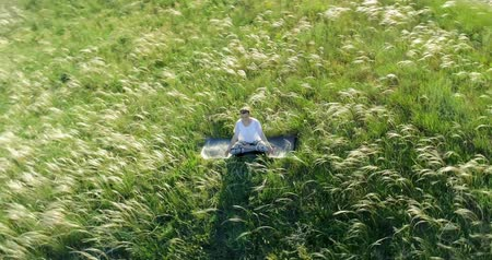 meditál : Girl meditates sitting on a beautiful green meadow