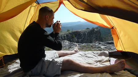 frescura : Man drinks from a mug in an camping outdoor