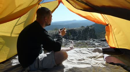 поход : Man drinks from a mug in an camping outdoor
