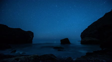 Time-lapse. Star trails above the rocky seashore
