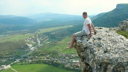 young man sits on the edge of a cliff Dostupné videozáznamy