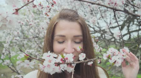 smell : Beautiful girl near blossoming tree in spring