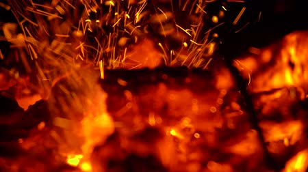 Iron poker stirs hot coals of burning close up