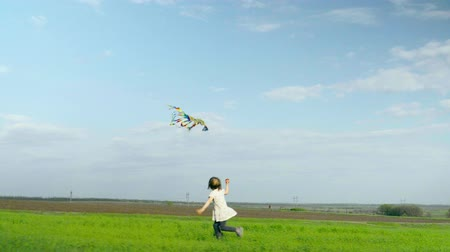 Cheerful little girl runs and playing with a kite