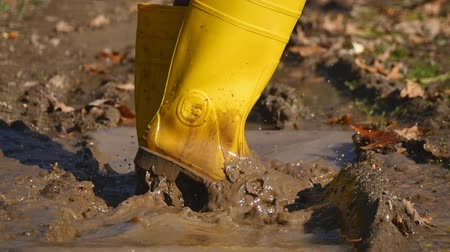 sujo : Dirty rubber boot steps into splashing dirty water in slow motion Vídeos