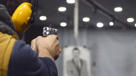 shooting range : Man shooting with a pistol at the shooting range, focus on the pistol in slow motion
