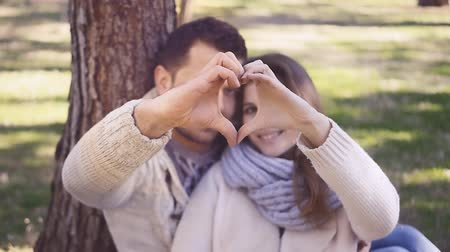 ve tvaru : Couple showing heart with their hands sitting in the park in spring, slow motion