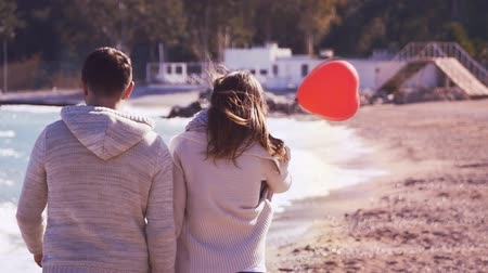 zadnice : Young couple holding their hands and walking away by the sea, with heart shaped balloon in slow motion