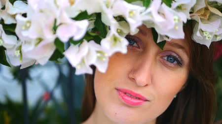 usual : Portrait of blue-eyed young woman with beautiful white berganville flowers above her head looks at the camera Stock Footage