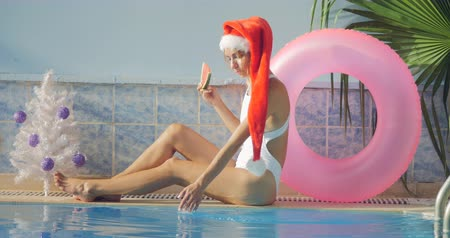 inflável : Young woman in long Christmas hat in swimsuit celebrating New Year with watermelon by the swimming pool. Winter vacation concept