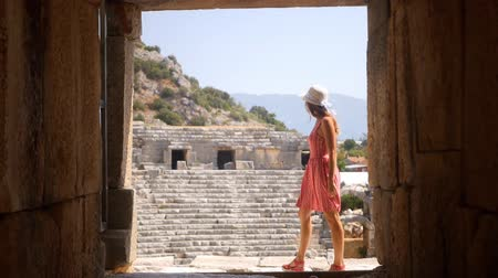 archeologický : Pretty woman walking in Antique Theater in ancient city Myra, Turkey. Turns around.
