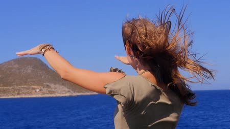 ветер : A young woman admires the sea from the deck of a ship. Enjoying the nature and travel vacation. Стоковые видеозаписи
