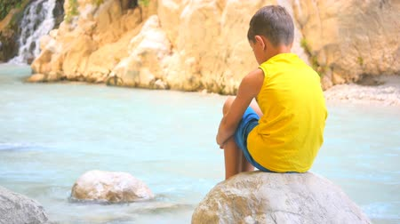 leisureactivity : Back view of child sitting alone on stone near the river