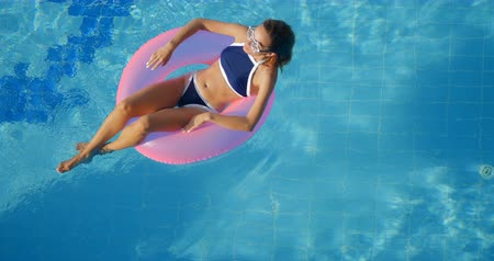 blue braid : Slim woman in star glasses relaxing in a swimming pool on the pink inflatable ring