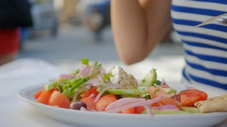 греческий : Closeup of womans hand eating Greece salad and drinking wine
