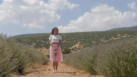 aromaterapia : Young woman in pink skirt standing straightly in the lavanda field in sunny day