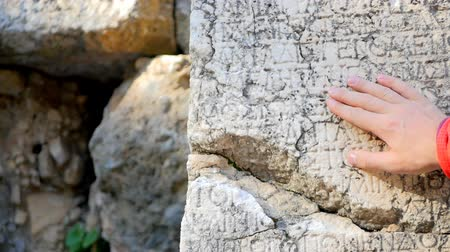 phaselis : Mans hand pointing at Ancient Greek script carved on stone plate, Phaselis, Turkey