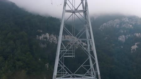 vago : View from a cabin to a cable car tower appearing from the fog. Low visibility at mist