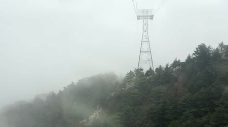 расплывчатый : View from a cabin to a cable car tower appearing from the fog. Low visibility at mist