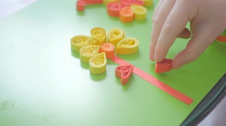 quilling : Child glues curly paper for quilling, flower shape.