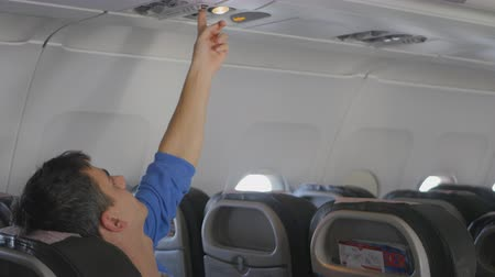 aeroespaço : passanger in aircraft switching air conditioning on the overhead console Vídeos