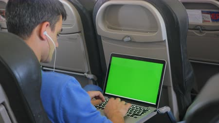 elszánt : Casually dressed young man working on laptop with green screen in aircraft cabin during his travel.
