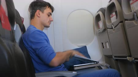 elszánt : Casually dressed young man working on laptop in aircraft cabin during his travel. Then closes laptop and sleeps.