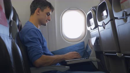 elszánt : Casually dressed young man working on laptop in aircraft cabin during his travel.
