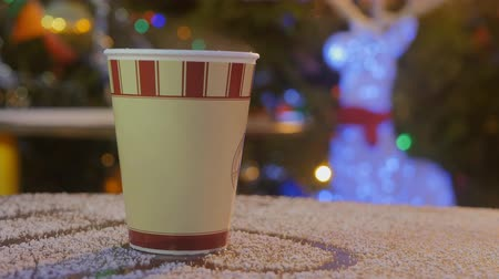 латте : take away coffee cup on snowy wooden table outdoors in Christmas market