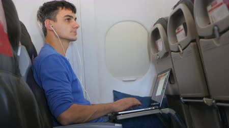 dedicado : Casually dressed young man working on laptop in aircraft cabin during his travel. Calling for stewardess but she passes by