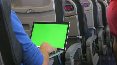 cabins : Casually dressed young man working on laptop with green screen in aircraft cabin during his travel.
