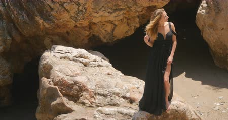 tengeri : Beautiful woman standing on the rock in windy weather in elegant cut out black dress