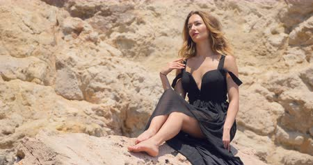 черные волосы : Beautiful woman sitting on the rock in windy weather in elegant cut out black dress Стоковые видеозаписи