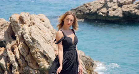 opalenizna : Outdoor summer view on young pretty woman standing on the rocks near the sea, enjoy her freedom, wearing stylish black elegant dress.