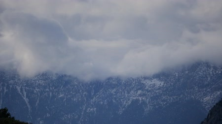 puffy cloud : Snowy mountain peaks in clouds in spring time. Turkey, Kemer Antalya Stock Footage