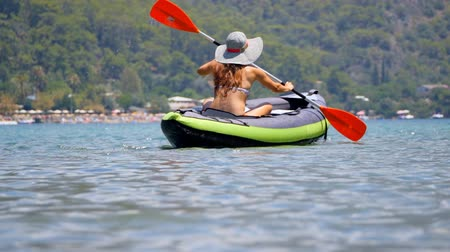 remo : Young woman in hat riding alone a canoe or kayaking in Oludeniz sea in Turkey.