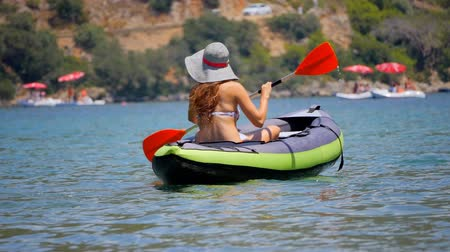 каноэ : Young woman in hat riding alone a canoe or kayaking in Oludeniz sea in Turkey.