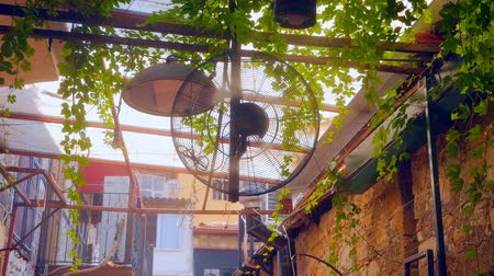 циркуляция : Outdoor fan blowing fresh air and spraying water at the restaurant Стоковые видеозаписи