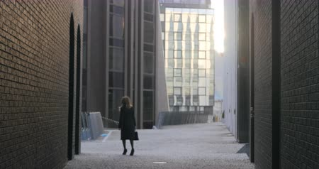 cansado : Young woman in casual black coat walking on the street with brick buildings. Backside view. Peek out the wall Stock Footage