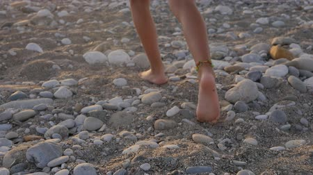 собственность : Closeup of child feet with beaded bracelets, on the beach at sunset time Стоковые видеозаписи