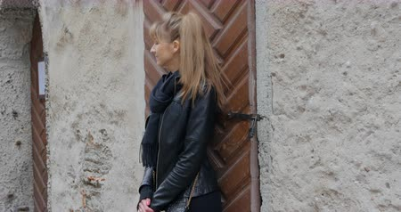 portaretrato : Young woman in black leather jacket standing near the stone wall Archivo de Video