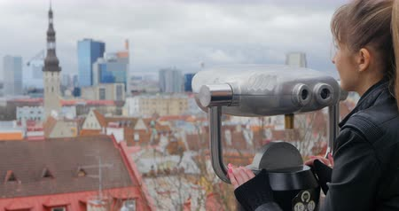 lookout point : Young woman in black jacket looking at coin operated telescope to the red roofs of Old City Tallinn, Estonia in spring time