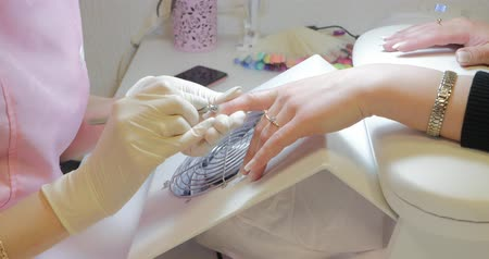 higiênico : Manicurist in disposable gloves using cuticle pusher for pushing cuticles on clients finger. Removing gel manicure.
