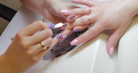 мастер : Closeup of manicurist hands using cuticle pusher for pushing cuticles on clients finger after applying color gel polish.