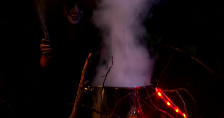 perverso : Wicked frightening witch with cane above the cauldron in dark forest . Halloween Horror Scene