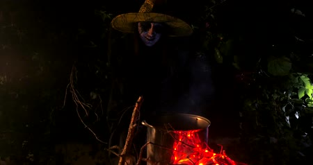 wicked : Wicked frightening witch with cane above the cauldron preparing potion in dark forest . Halloween Horror Scene