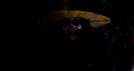 soletrar : Wicked frightening witch with cane above the cauldron in dark forest . Halloween Horror Scene