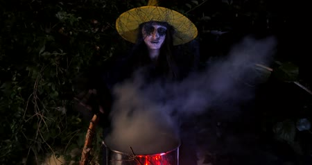 wicked : Wicked frightening witch hexing with cane above the cauldron in dark forest . Halloween Horror Scene Stock Footage
