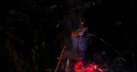 wicked : Wicked frightening witch with cane above the cauldron in dark forest stirs her potion . Halloween Horror Scene